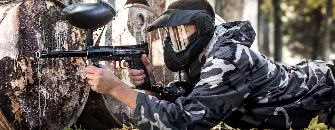 man with gun playing paintball